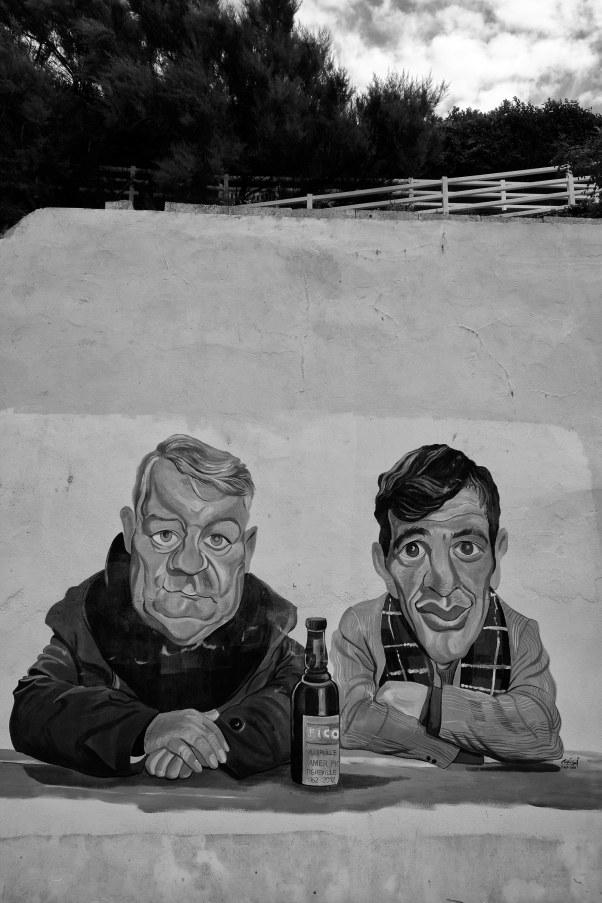 """Wandbild eines unbekannten Künstlers von Jean Gabin und Jean-Paul Belmondo in Villerville (Normandie), wo die beiden 1962 zusammen den Film """"Un singe en hiver"""" (""""Ein Affe im Winter"""") drehten - © Michael Kneffel"""
